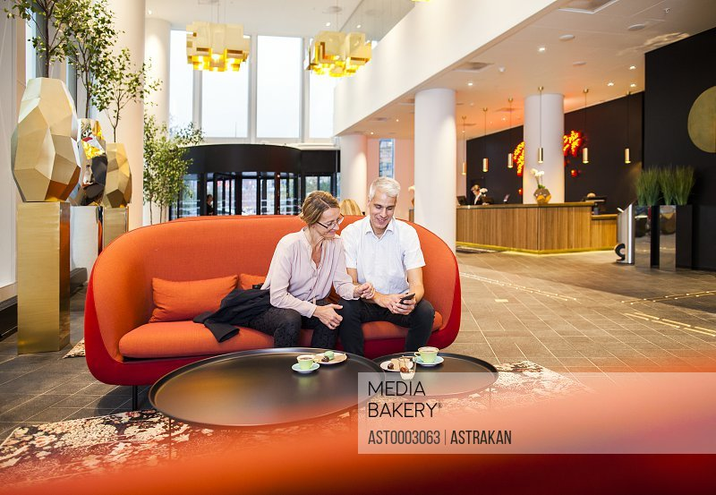 Business people using mobile phone while sitting on orange couch at hotel lobby