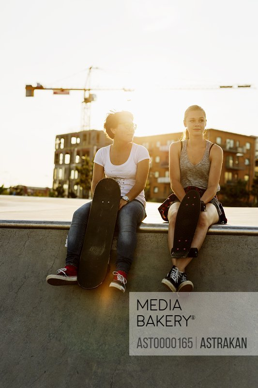 Full length of relaxed female friends sitting at edge of skateboard ramp