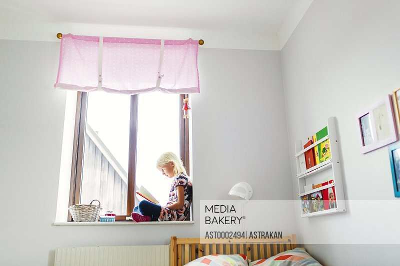 Full length side view of girl reading book on window sill