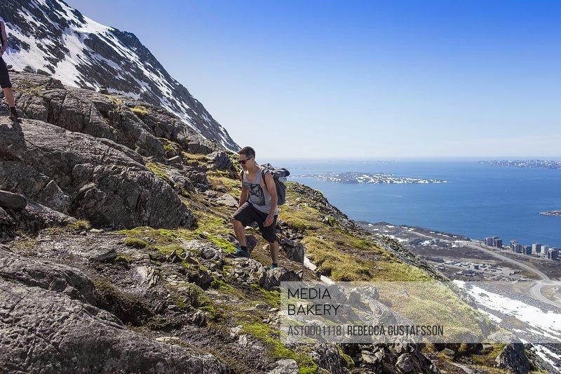Hiker walking on rocky mountain at seaside