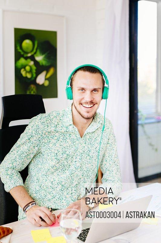 Portrait of confident businessman wearing headphones at office desk