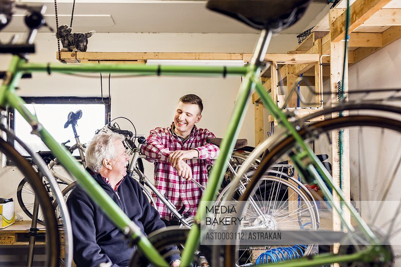 Happy father and son talking in bicycle shop