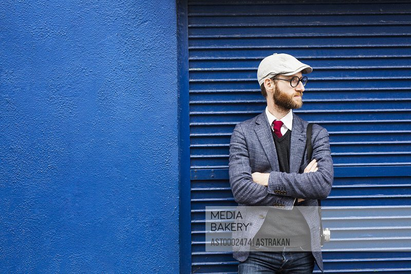 Thoughtful man standing arms crossed against blue shutter