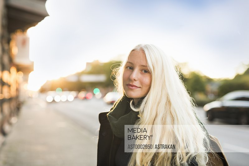 Portrait of teenage girl standing on footpath against sky during sunset