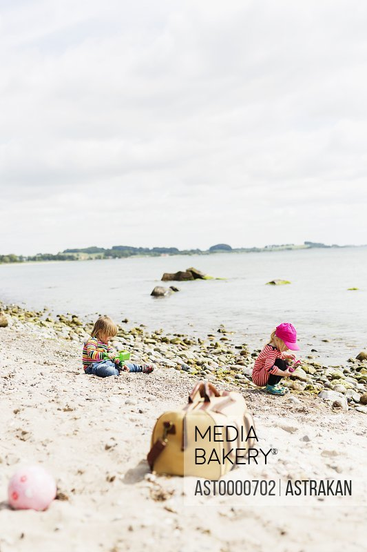 Children playing on beach against cloudy sky