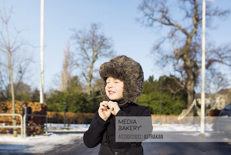 Boy wearing fur hat on street during winter