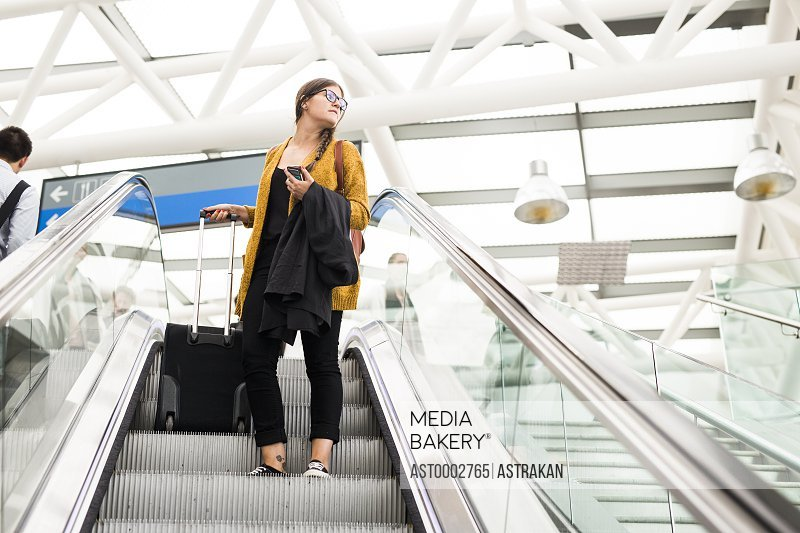 Low angle view of businesswoman with luggage on escalator at airport