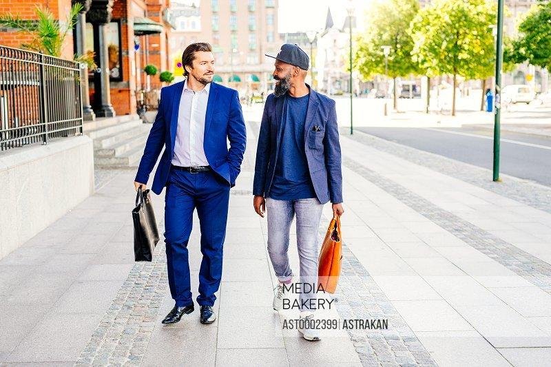 Full length of businessmen walking on sidewalk outside railroad station