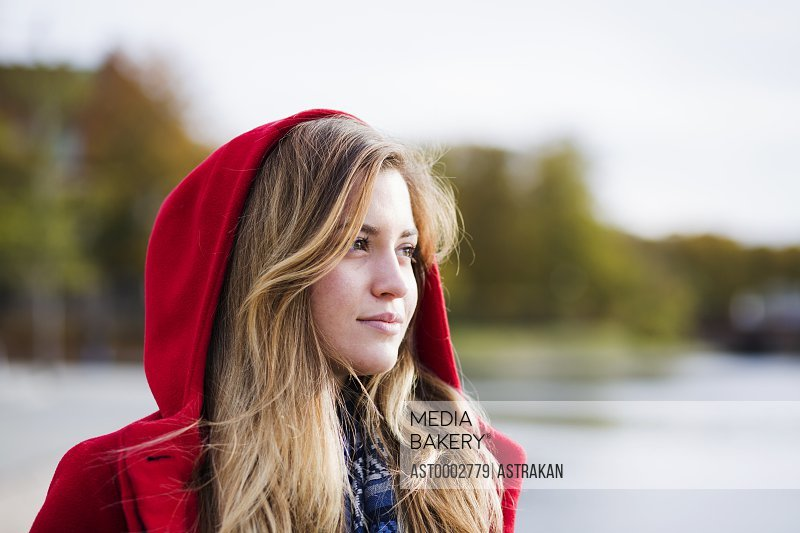 Thoughtful young woman wearing hooded jacket outdoors