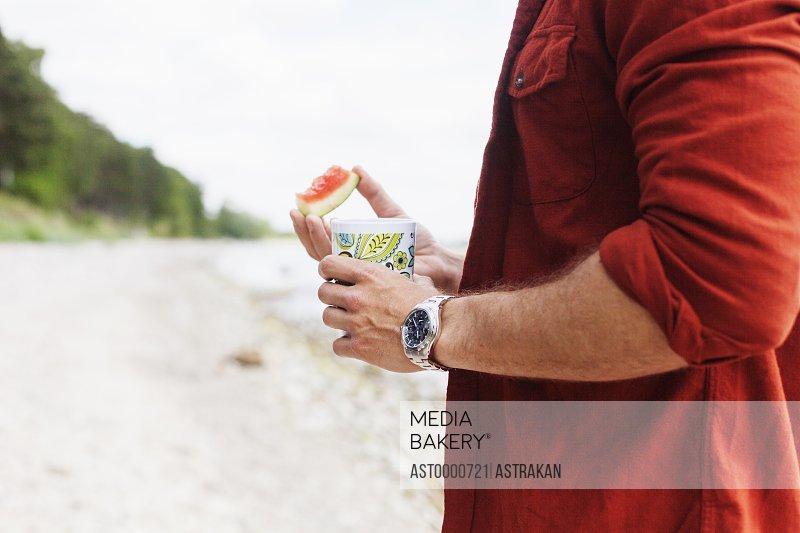 Man holding drink at beach