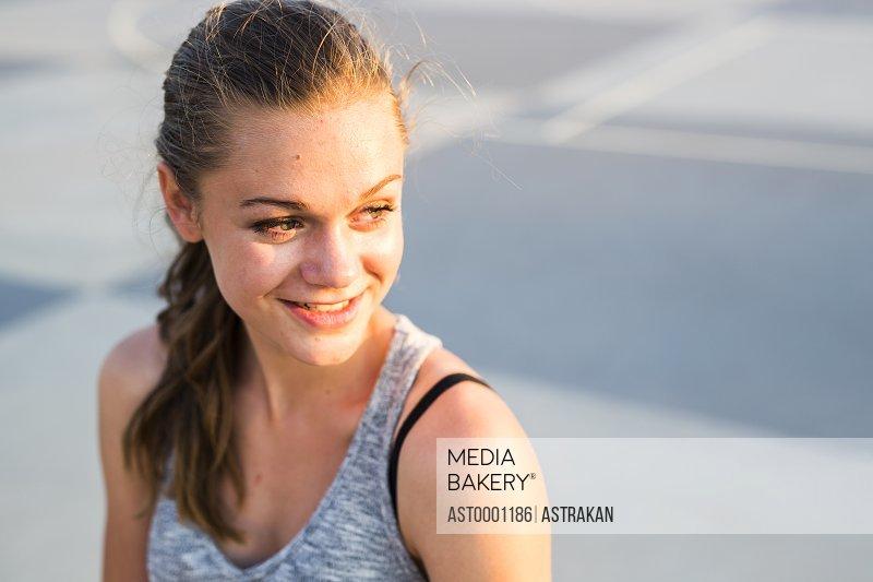 Happy teenage girl looking away at skate park