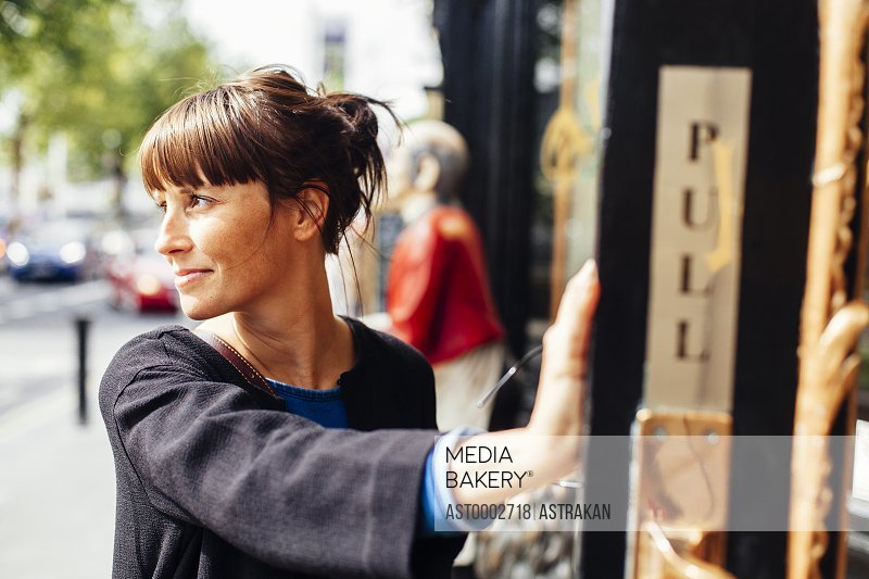 Smiling woman looking away while standing outside restaurant