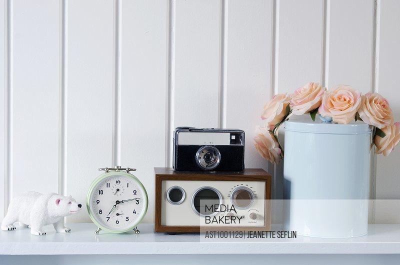 Vintage clock and camera on shelf