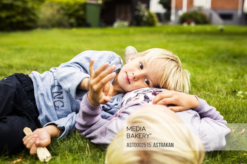 Boy lying on his sister's stomach in yard