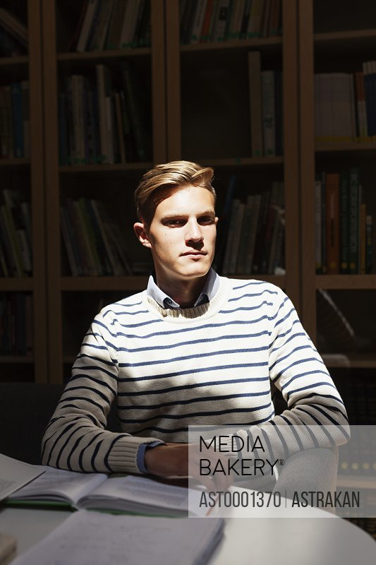Portrait of young man with book at desk in university library