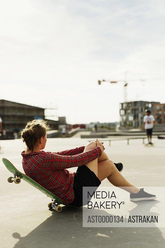 Full length side view of woman relaxing on skateboard at skate park