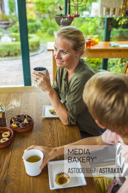 Happy woman with son having coffee at table