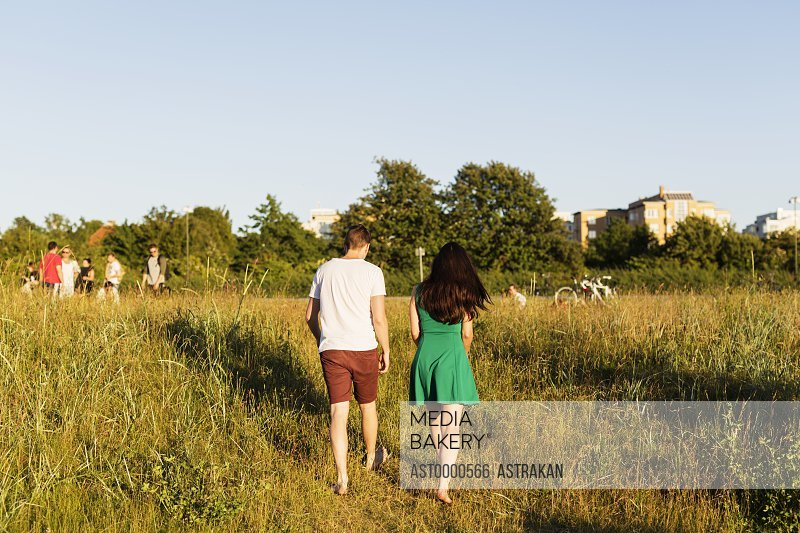 Rear view of couple walking on grassy field against clear sky