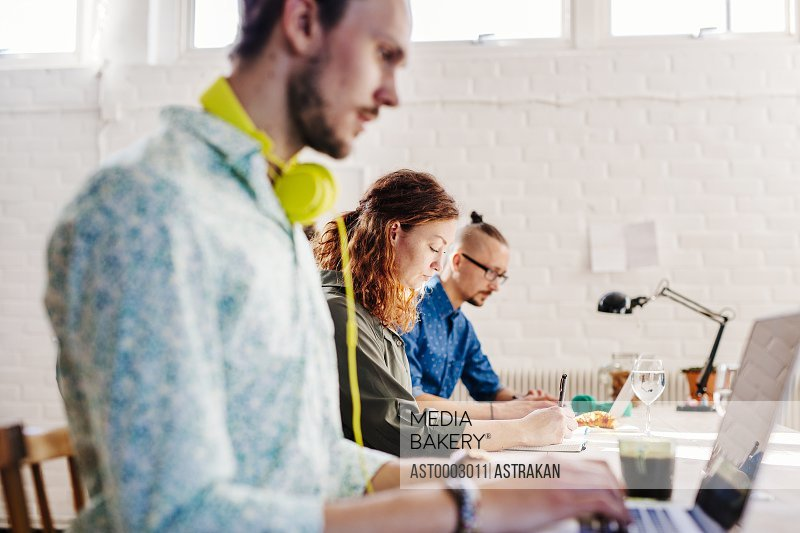 Mid adult businesswoman with male colleagues working at table in creative office