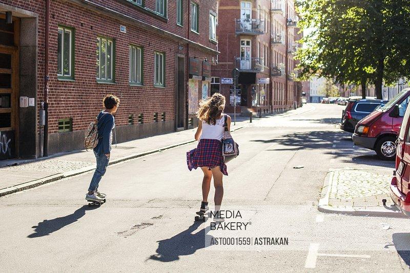 Rear view of girls skateboarding on street by buildings