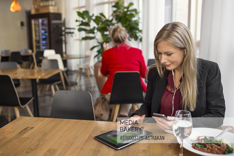 Businesswoman using digital tablet while talking through earphones at restaurant