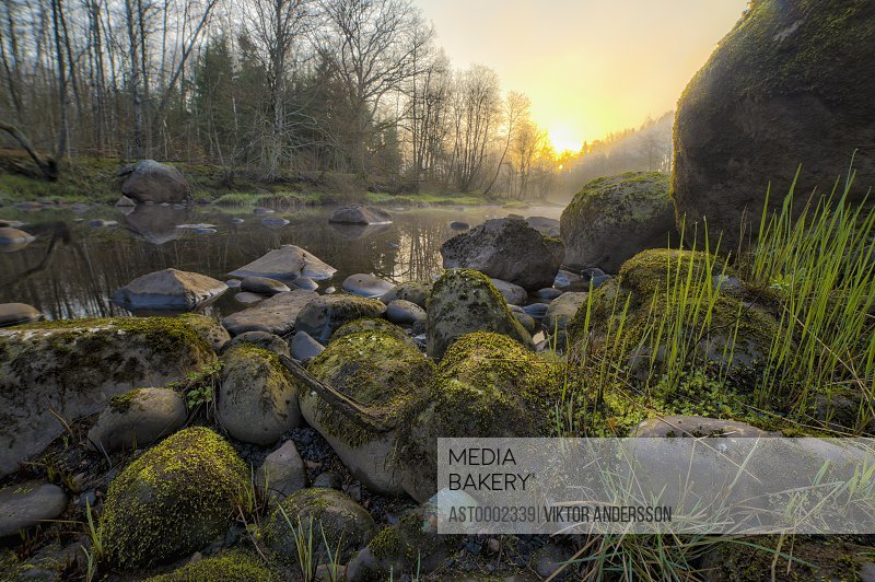 Stream flowing by rocks on field against sky during sunset