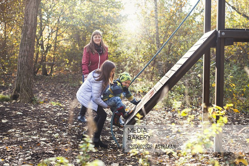 Mother watching children climbing obstacle wall in forest
