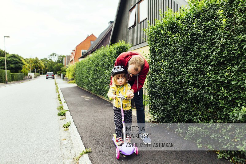 Full length of man teaching daughter to ride push scooter on sidewalk