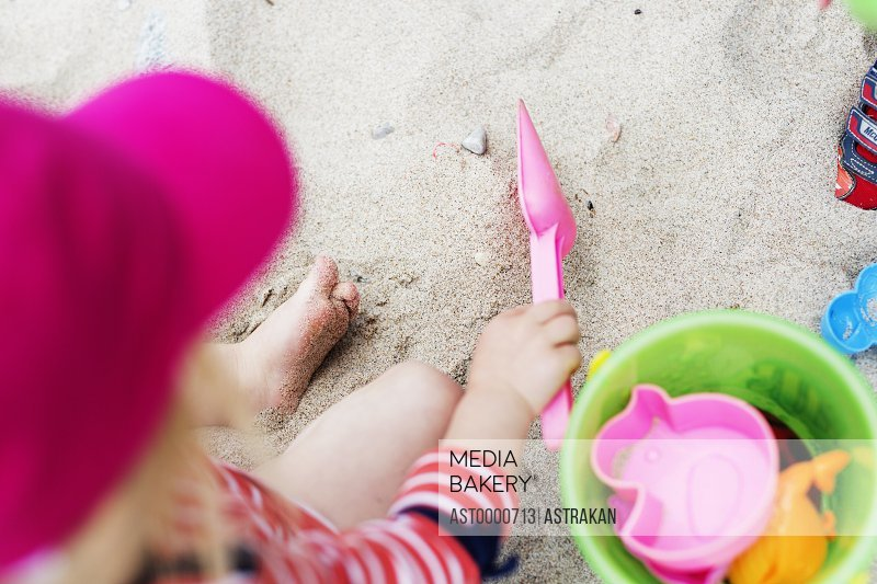 High angle view of girl playing with toys on sand at beach