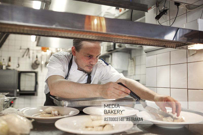 Chef serving food in plate at restaurant