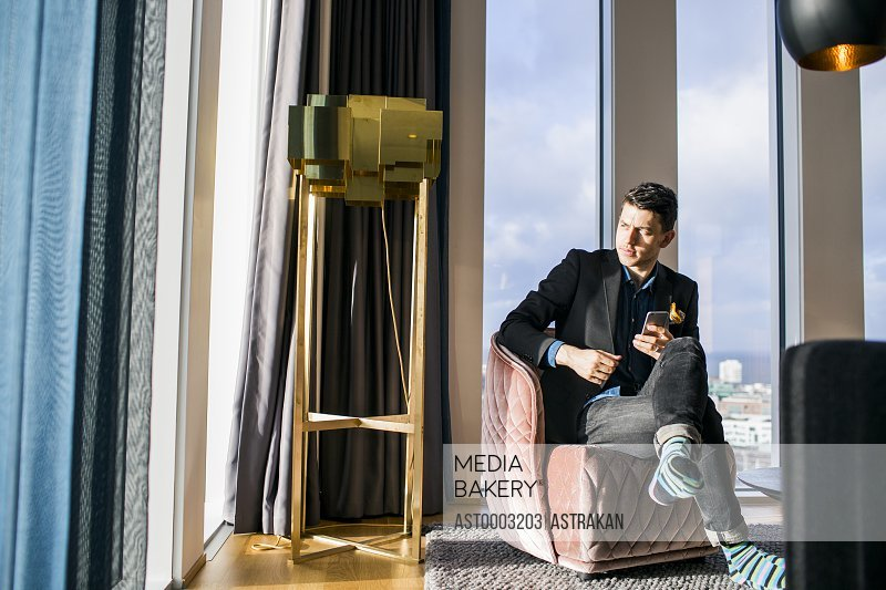 Businessman sitting on chair with phone looking through window at hotel room