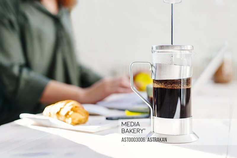 Coffee maker on table with businesswoman in background at office