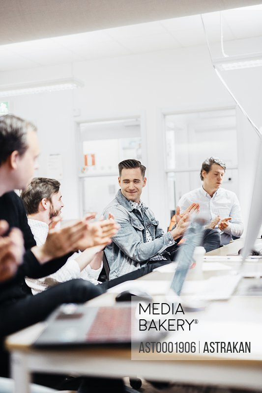 Happy media students clapping while sitting at computer desk in classroom