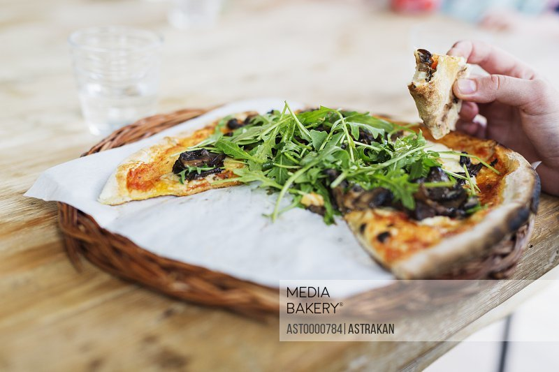 Cropped image of person holding pizza slice at cafe table
