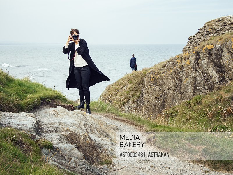 Full length of woman photographing while standing on rock by sea