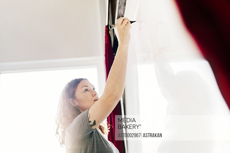 Low angle view of businesswoman writing on whiteboard in office