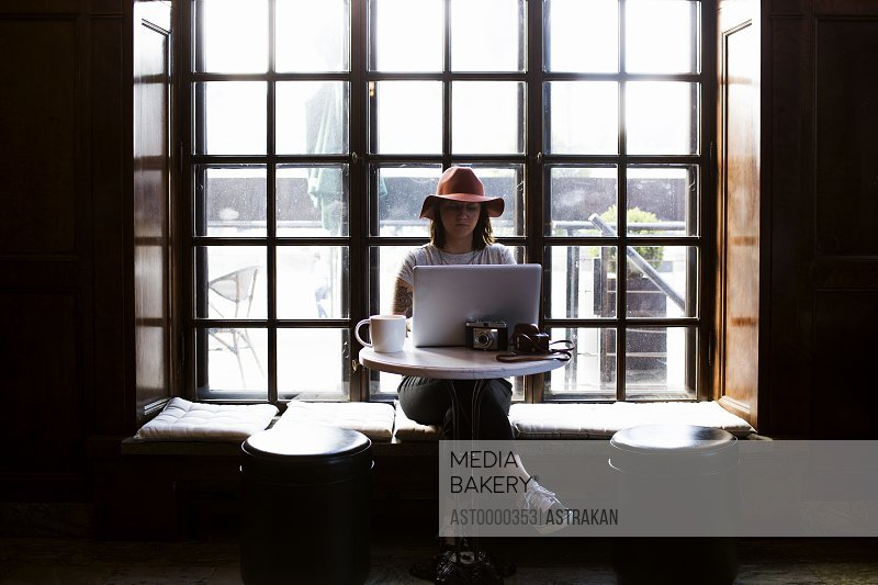 Female freelancer using laptop while sitting by window in cafe