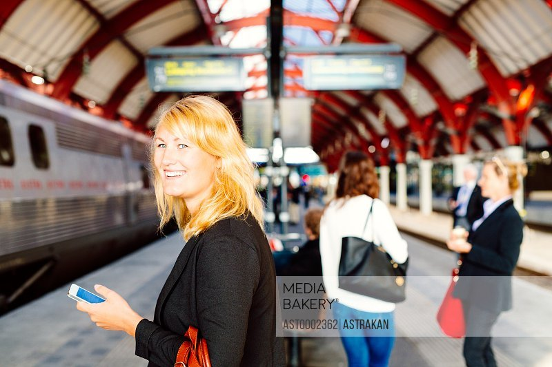 Side view of happy businesswoman holding smart phone while standing at railway station