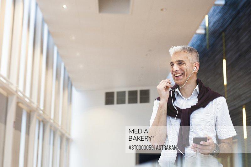 Happy businessman talking through headphones at hotel lobby