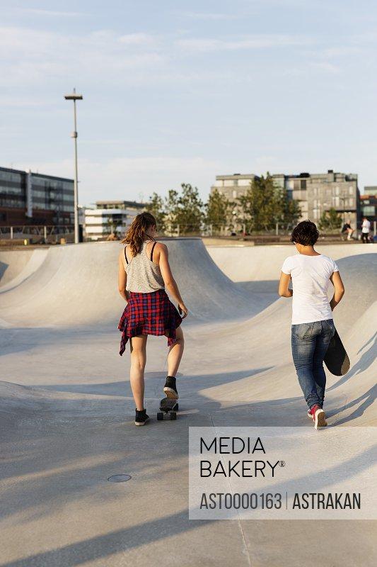 Full length rear view of teenage girls skateboarding in skate park