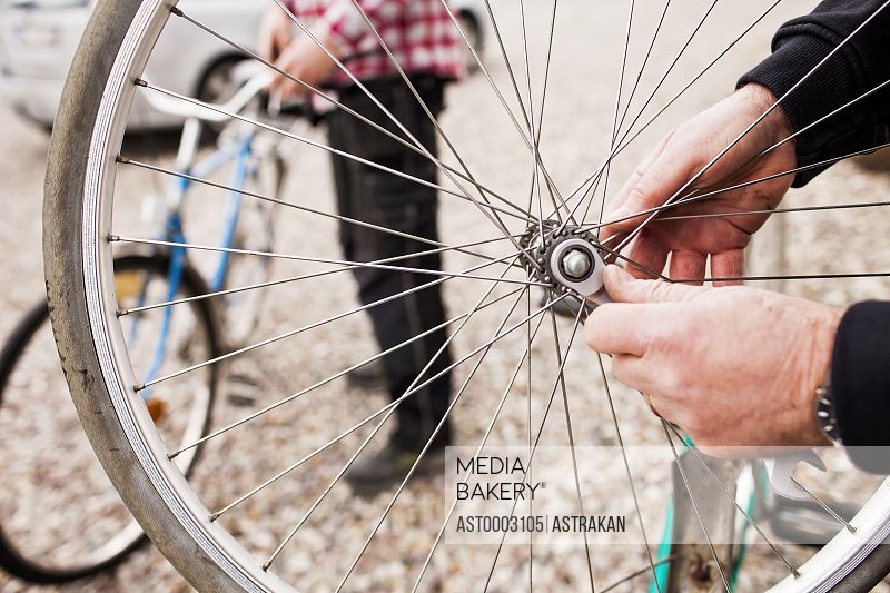 Cropped image of senior man repairing bicycle tire with son working in background