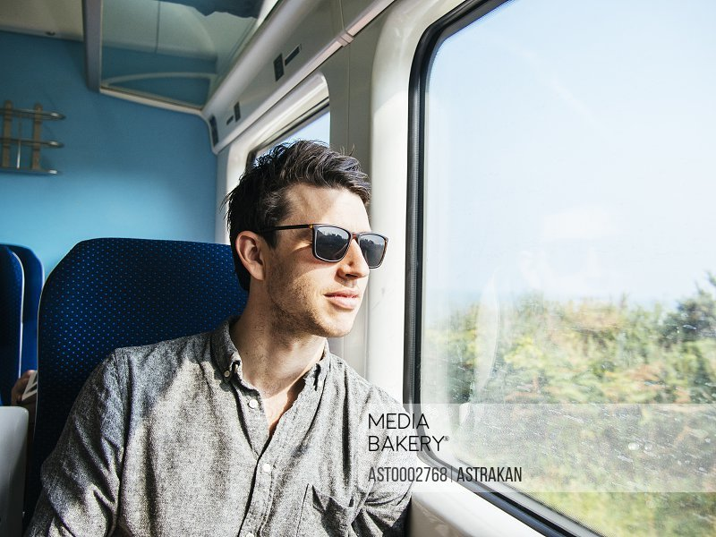 Thoughtful businessman in sunglasses looking through train window