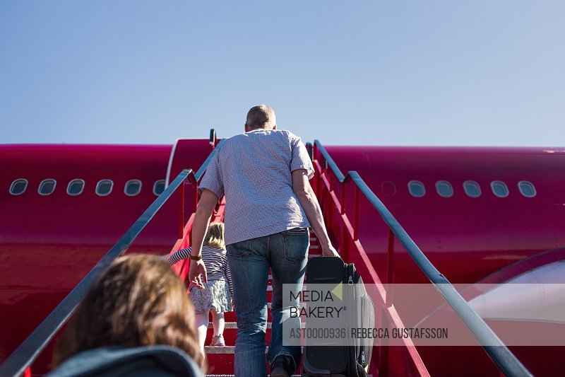 Low angle view of people walking on staircase towards airplane