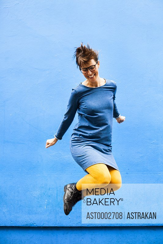 Full length of cheerful woman jumping against blue wall