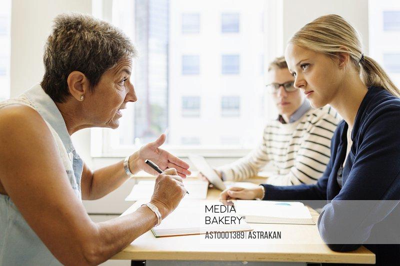 Mature teacher teaching university students at desk in classroom