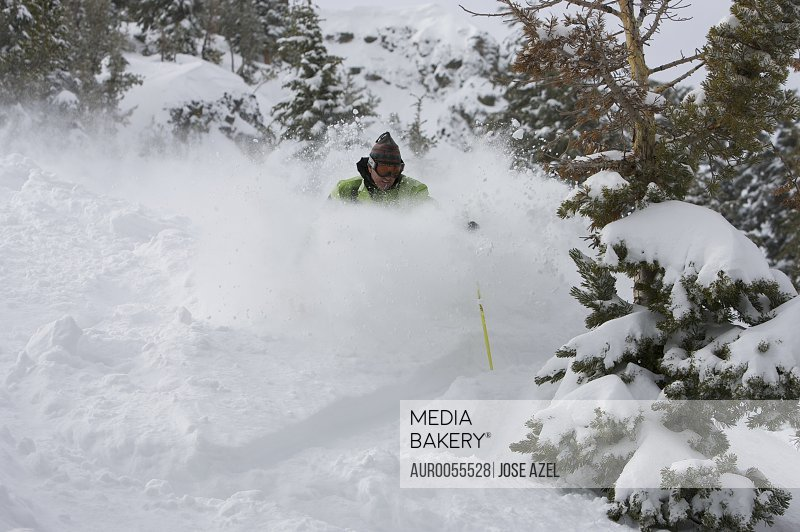 A skier descends a snowy slope through deep powder on a beautiful day in Kirkwood, California.<br><br><span style='color: red'>Editorial Use Only.</span><br><br>