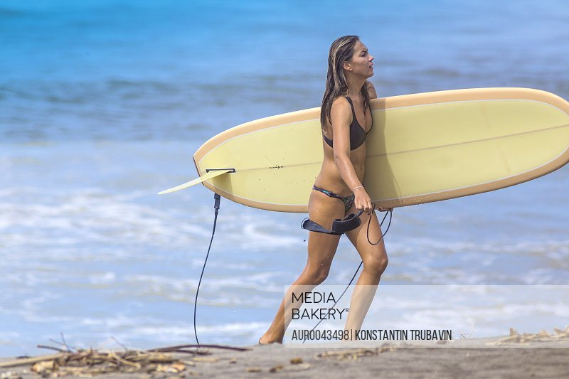 Young woman with surfboard on a beach.