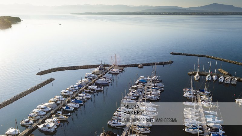 aerial view on the marina in Prangins with lots of boats and the Alps in the background, Switzerland