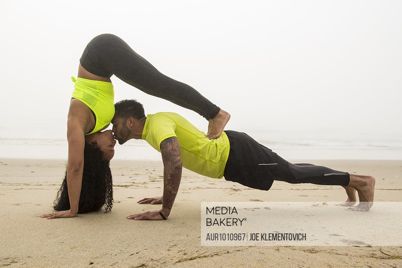 Adult couple kissing while exercising on sandy coastal beach during foggy weather, Hampton, New Hampshire, USA