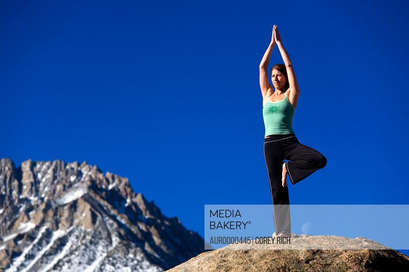 A woman doing yoga on top of a boulder.